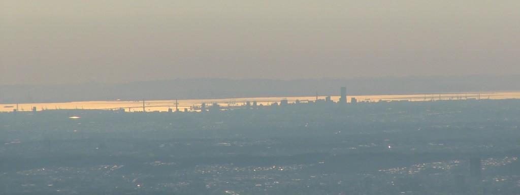 更に時間がたつと東京湾が陽の光を反射して輝きを増し、横浜港やランドマークタワーがシルエットになります。元旦の御来光はこの横浜と新宿の中間の羽田沖から昇ります。