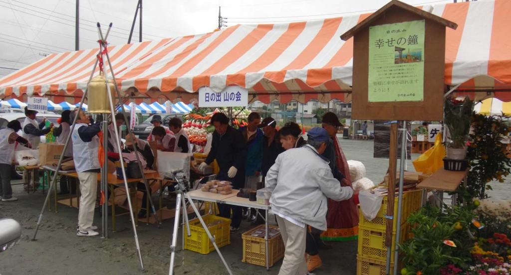 日の出山の会のブースは、日の出山山頂から降ろしてきた幸せの鐘を設置し、清酒幸せの鐘やキウイ、竹細工などを販売し、テント内には写真を展示しました。