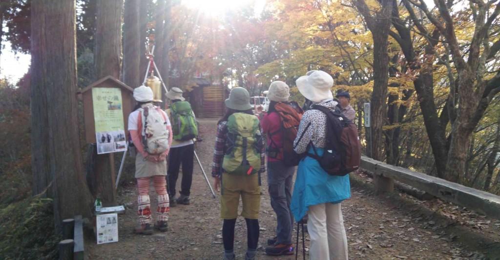 日の出山に登頂された皇太子殿下と、幸せの鐘のいわれを読む登山者。