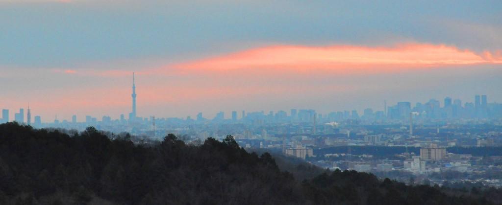東に広がる都心は雲に覆われ雲間が赤く染まり、日の出の時間が来たことを知らせている。