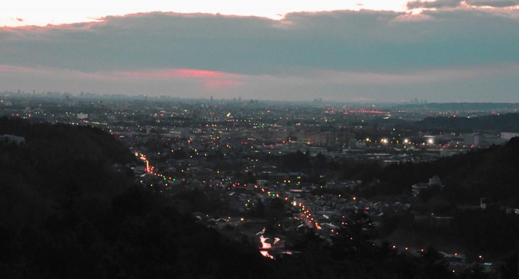 日の出前の空は地平線を雲が覆い、地上はまだ街路灯が消えず、眠りから覚めていません。
