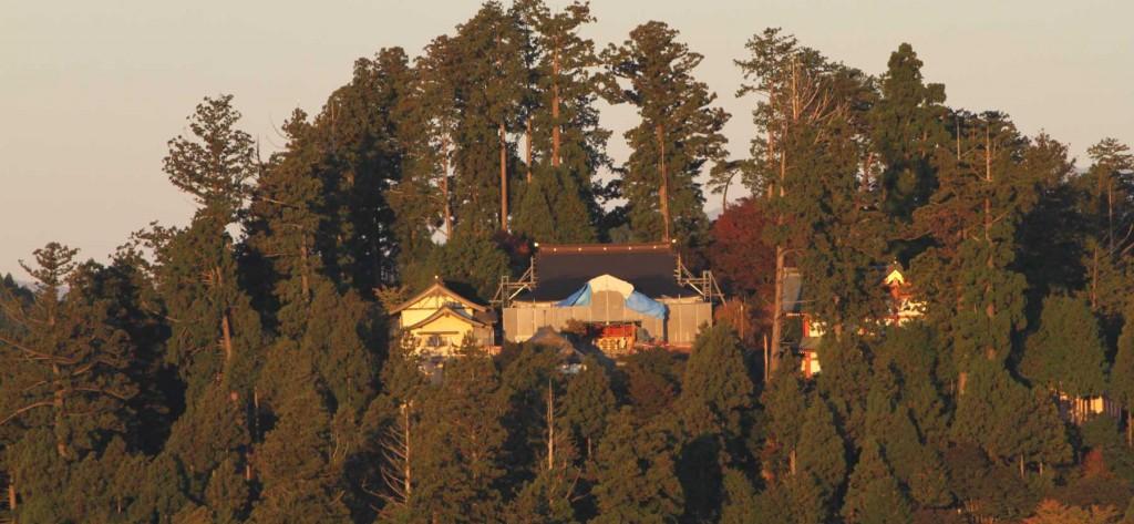 日の出山から拝する御岳神社は朝日に映えている。今は改装工事中で、シートに覆われている