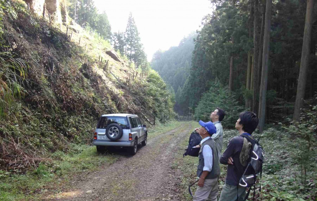 麻生尾根への取り付き点で大岩を見上げる山主さん、林務関係者、ボルダラー(ボルダリング、フリークライムの一種)。