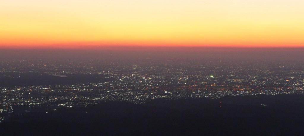 日の出前の山頂から。ビルの灯は消え、街路灯がまだ消え残る都心は、が程よくかかり、霞のフィルター効果で素晴らしい夜明けの空だ。